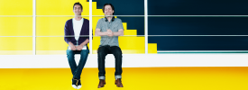 Two happy men against a yellow background in an office