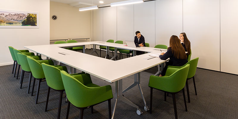 A man and two women are having a discussion around a large meeting room table